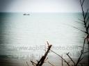 Sur une plage déserte, seule présence cette barque et son parasol rouge.